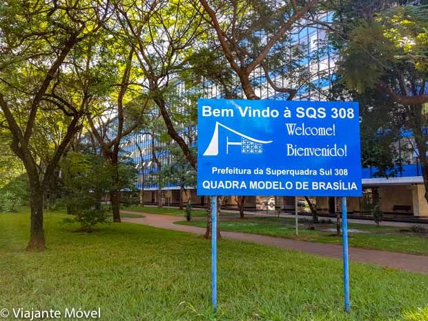 """Placa azul na entrada da 308 sul Quadra Modelo de Brasília, escrito """"Bem vindo a SQS 308. Welcome! Bienvenido! Prefeitura da Superquadra sul 308. Quadra modelo de Brasília."""
